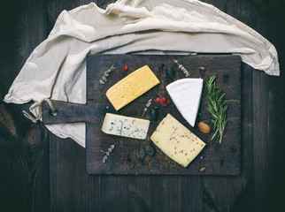 pieces of different cheeses on a brown wooden board