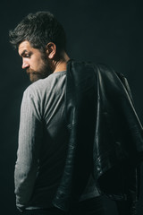 View from behind bearded man carrying black leather jacket on shoulder. Casual attractive handsome man with black leather jacket on shoulder and wearing gray shirt.