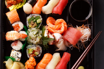 fresh traditional Japanese sushi with scallops, tuna, shrimp, mix rolls, octopus sashimi, salmon, tuna, top view. food delivery. A large set of sushi, rolls, sashimi in the package.