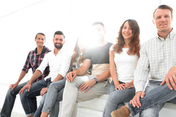 young creative people sitting on chairs in waiting room