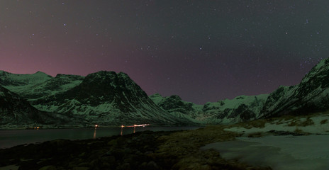Clear sky during a starry night above the mountains surrounding a Norwegian fjord