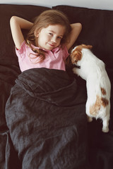 Little girl with a puppy lying in the bad at home. Jack Russell Terrier Puppy wants to wake up a child in the morning.