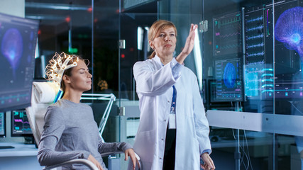 Woman Wearing Brainwave Scanning Headset Sits in a Chair while Scientist Swipes Augmented Reality Screen Showing Brain Model and EEG Data. In the Modern Brain Study Laboratory.