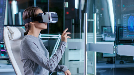 In Laboratory Scientist Wearing Virtual Reality Headset Sitting in a Chair Interacts With Monitors Showing Brain Activity, and Neurological Data. Modern Brain Study/ Neurological Research Center.