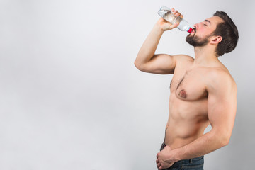 Nice and wonderful picture of handsome man standing very close to a white wall and drinking some water from the bottle. He is enjoying the moment. Isolated on white background