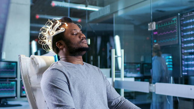Man Wearing Brainwave Scanning Headset Sits in a Chair while Scientist Adjusts the Device. In the Modern Brain Study Laboratory Monitors Show EEG Reading and Brain Model.