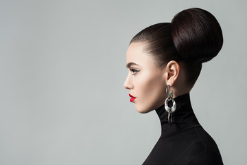 Foto auf Acrylglas Friseur Fashion Portrait of Elegant Young Woman with Hair Bun Hairstyle and Eyeliner Make up. Cute Female Model wearing Black Roll Neck Jersey, Profile Portrait.