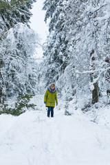 A young woman is walking through the winter forest