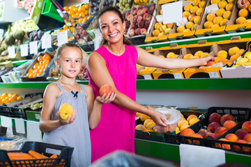 mother with girl taking peaches on market .