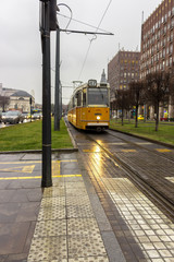 Budapest, Hungary - 02/22/2018: Old yellow tram, car traffic and buildings on city street. Transport and travel concept. Train rails and city road. Budapest landmark and transportation. Cityscape.