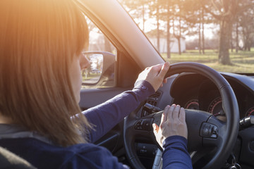 Closeup of woman hand pressing the horn button while driving a car, female driver concept