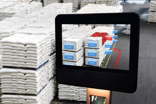 Industry 4.0,Augmented reality and smart logistic , robo advisor technology concept. Robot display screen with AR application for check order pick time in smart factory warehouse.