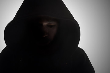 Man in hood / Hooded man in shadow on gray background.