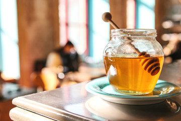 Tasty honey in a glass jar with a special wooden spoon in the foreground in a cafe with a blurry background.