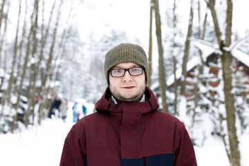 Sport style man portrait in the winter forest. Snow adventure