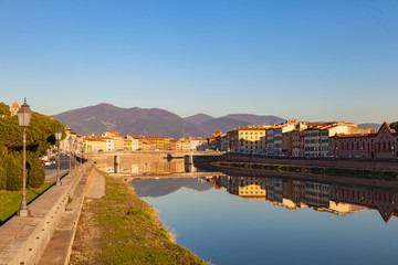 Arno river embankment with colorful old houses, view from Ponte della Citadella. Picturesque medieval town of Pisa, Tuscany, Italy.