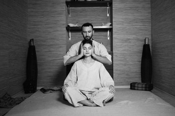 man and woman in white sitting in the lotus position and relax. Tibetan massage. Health. meditation