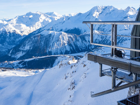 Gondola lift cabin of ski-lift in the ski resort in the early morning at dawn with mountain peak in the distance. Winter snowboard and skiing concept. France, Courchevel, 2018