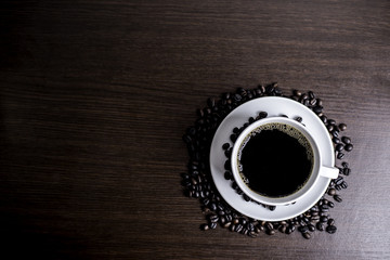 Black coffee in white cup and coffee bean on wood table background.