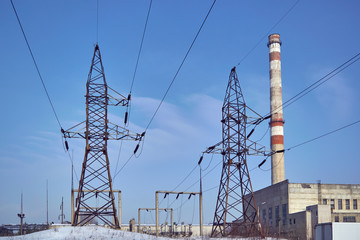 Supports high voltage transmission lines and pipe thermal power station. In the background is a clear blue sky. The building of the thermal power station. On supports of wire or cable.