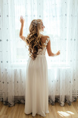 Blonde bride poses before a bright window in the room