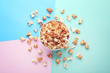 Caramel popcorn in bowl on colorful background
