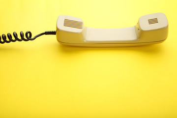 Beige telephone handset on yellow background