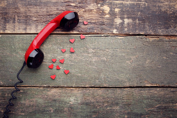 Telephone handset with red hearts on wooden table