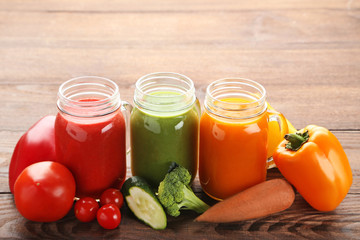 Vegetables smoothie in jars on wooden table