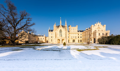 The Lednice castle panorama in snow, winter. Beautiful old historical architecture, blue sky. Czech republic unesco