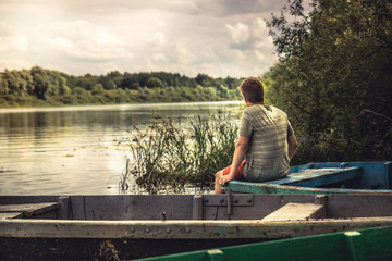 Teenager boy lonely contemplation countryside scenery on river boat during countryside summer holidays