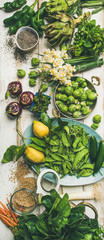 Spring healthy vegan food cooking ingredients. Flat-lay of vegetables, fruit, seeds, sprouts, flowers, greens over white wooden background, top view, vertical composition. Clean eating food concept