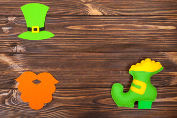 St. Patrick's Day theme colorful horizontal banner. Green leprechaun hat, beard and shoe with gold on brown wooden background. Felt craft elements. Copy space. For greeting card,congratulation banner