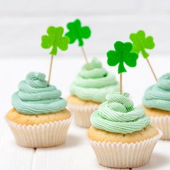 St. Patrick's Day theme colorful horizontal banner. Cupcakes decorated with green buttercream and craft felt decorations in form of shamrock leaves on white background. Copy space. For greeting card