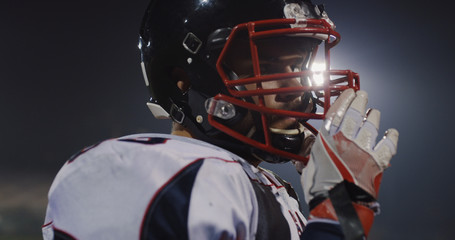 American Football Player Putting On Helmet on large stadium with lights in background