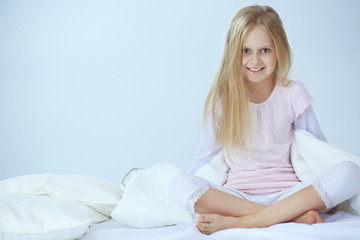 Little girl in the bedroom is sitting on the bed. Little girl is wearing a pajamas and sitting in bed