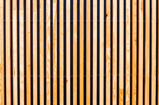 background of wooden boards, slats. Modern architecture, urban. Wooden texture. Designer background