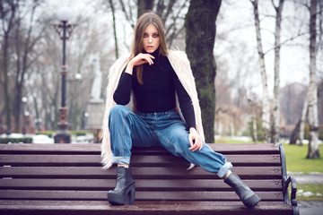 Girl in casual fashion clothes. On the street there is snow. Gloomy makeup. Fashionable woman. Casual wear. Trend clothing. Toned image.