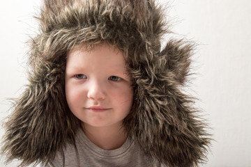 Happy child playing at home. The funny guy put on a warm fur hat and admires himself. Close-up. Portrait with emotions.