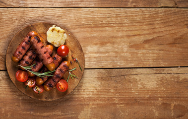 Festive cocktail sausages wrapped in crispy smoked bacon commonly known as 'Pigs in Blankets' on wooden background