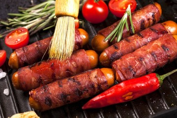 Festive cocktail sausages wrapped in crispy smoked bacon commonly known as 'Pigs in Blankets' in black pan