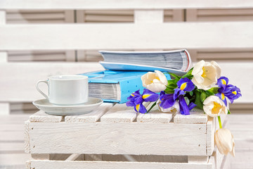 Spring background!A bouquet of irises, photo albums and a cup on a wooden background.