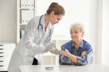 Doctor measuring blood sugar level of diabetic patient in clinic