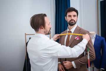 Tailor measuring client for custom made suit in atelier