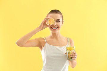 Beautiful young woman with glass of lemonade on color background