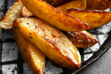 Plate with tasty potato wedges, closeup