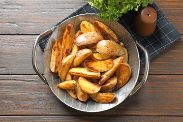 Dish with tasty potato wedges on table