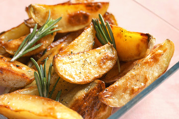 Dish with tasty potato wedges, closeup