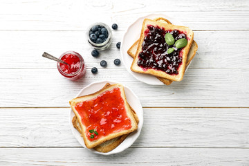 Delicious toasts with sweet jams on wooden background