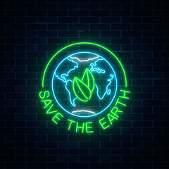 Glowing neon sign of world earth day with leaves in globe symbol and text on dark brick wall background.